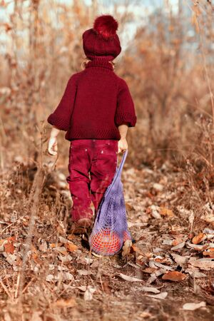 four year old girl in red knitted sweater, trousers and beret walks with her back to the yellow autumn leaves in the park, in her hand is natural bag made of cotton with pumpkin