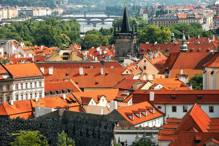 cityscape of Prague, red and yellow tiled roofs of city from above on sunny day