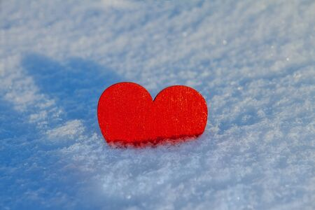 wooden red heart lies half in white snow on a sunny day