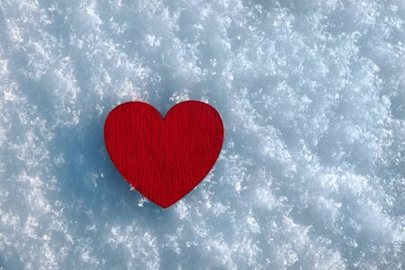 wooden red heart lies on snow on sunny day in winter