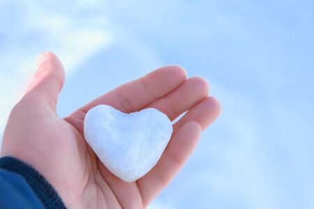 ice small snow heart in open childrens palm on light blue background copyspace Фото со стока