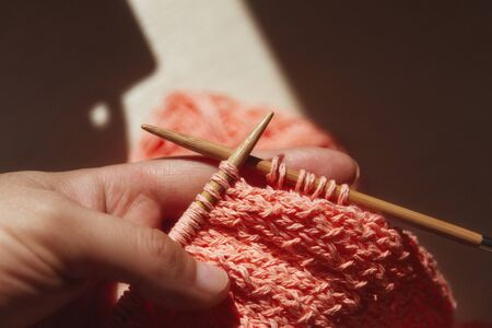female hands with knitting coral color, needles and knitted thing in the process of knitting in the sunlight around the shadow