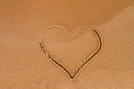 A cast of heart on wet yellow sand, washes away water, concept of love, parting and inconstancy, copyspace