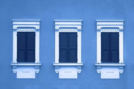 tinted blue three wooden window with shutters in white frame on wall