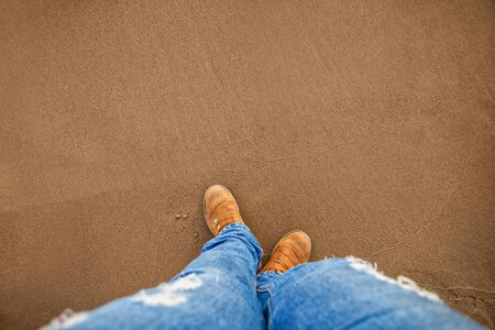 female legs in casual clothes blue jeans and leather brown boots on wet yellow sand on the beach top view from the first person
