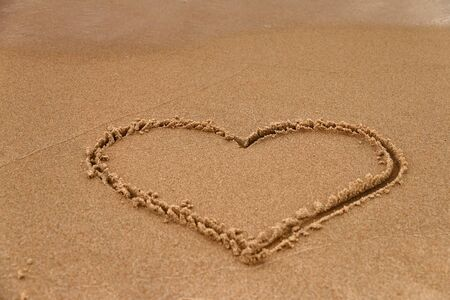 Hand-drawn heart shape symbol of love on wet yellow sand on beach, copy space