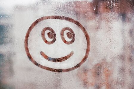 Happy smile face painted on window flooded with raindrops on blur glass background in city