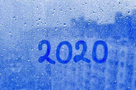 numbers 2020 of new year paint with finger on splashed by rain foggy glass on blue window