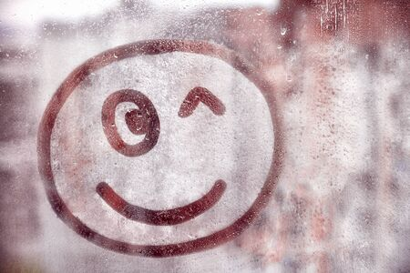 Happy smile face winks painted on window flooded with raindrops on blur red glass background in city Фото со стока