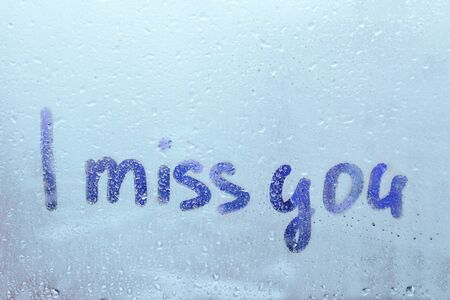 Handwritten word I miss you on misted glass on window flooded with raindrops on blue cloudy background