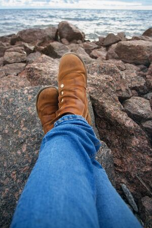 Womens legs in blue jeans and brown leather boots on the stones