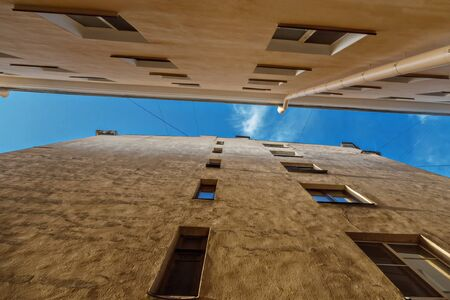 two residential buildings in the old courtyard, bottom view, strip of blue sky, drainpipe, copy space