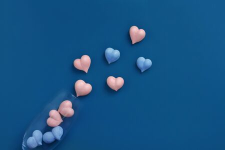 pink and blue heart-shaped meringue scattered dropped out of champagne glass on blue background Фото со стока