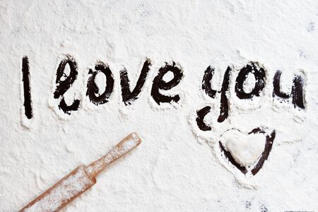 Words I love you hand-painted on a dark table covered with white flour, wooden rolling pin lies diagonally, cooking for lover