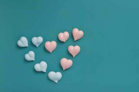 small meringues of pink and blue hearts are laid out in a big heart on a mint background Фото со стока