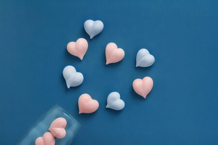 pink and blue heart-shaped meringue scattered dropped out of champagne glass on blue background, concept gender equality, love