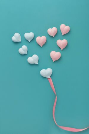 ten small meringues of pink and blue hearts are laid out in a big heart with pink fabric ribbon on mint background, vertical, concept gender equality, love