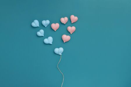 sweet meringue dainty pink and blue hearts laid out in big heart on turquoise background copy space on right