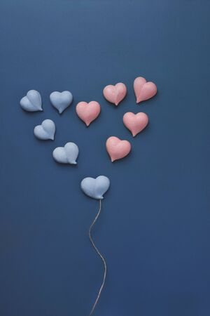 ten small meringues of pink and blue hearts are laid out in big heart with with rope made of natural twine like balloon on blue background, vertical, concept gender equality, love