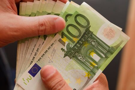 one hundred euro banknotes lie fan in male fingers close up