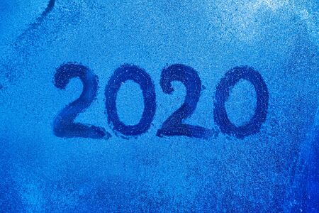 numbers 2020 of new year paint with finger on splashed by rain foggy glass on on frozen winter window, copy spase