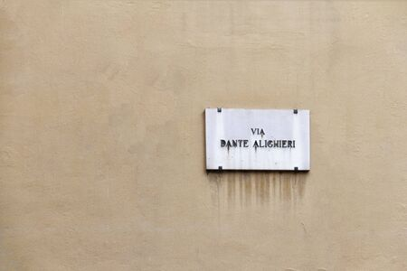 old Dante Alighieri street nameplate on ancient yellow wall in Florence in Italy