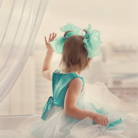 little girl of three years with blue bows and dress looks and touches the window in hand with blur