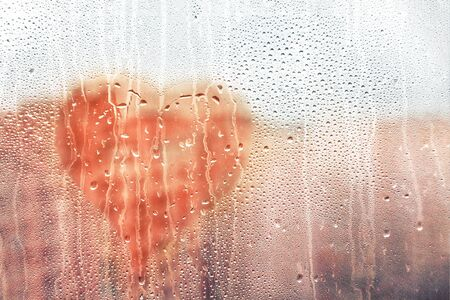 Hand drawn speech buble sunny heart shape painted on glass wet window with drops of rain in city, copy space