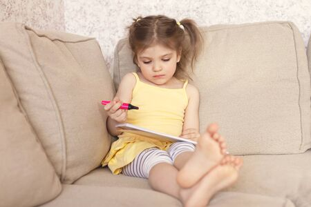 3 years old girl in a yellow dress and striped white and blue pants sits on a brown natural sofa, draws with a red felt-tip pen in an album, concept education, learning, homework, busy