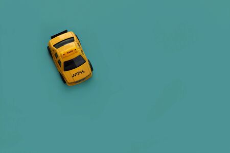 toy yellow car with taxi on the left side of turquoise background. Concept