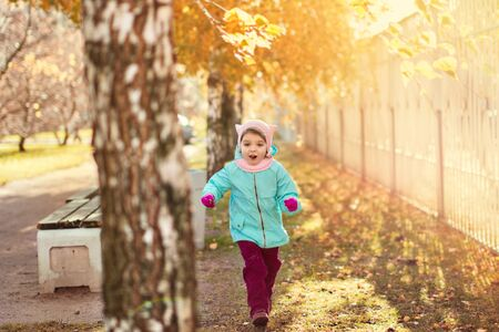 little girl 3 years in blue jacket, red pants, fur hat laughs and runs on the yellow foliage in autumn park