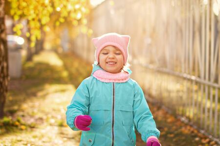 little child girl 4 years in blue jacket, red pants, fur hat laughs and smiling with eyes closed on the yellow foliage in autumn park