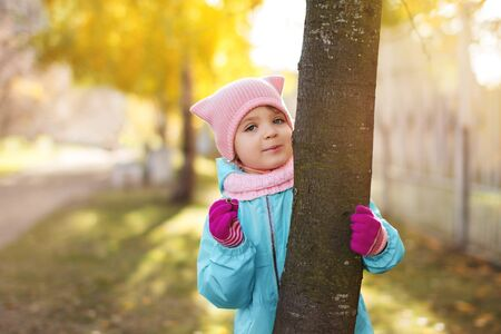 little child girl 4 years in blue jacket, red pants, fur hat smiles and peeps fervently from behind tree, dried twig in fingers on the yellow foliage in autumn park