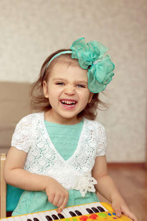 Little child girl 4 years old Caucasian sits on chair in the room, plays piano and laughs