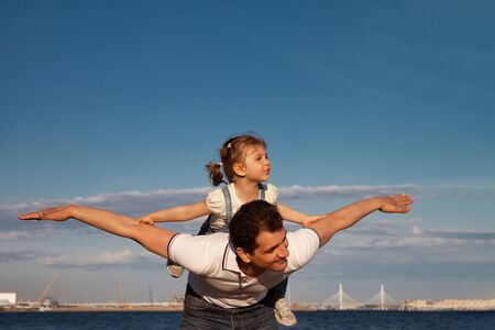 little girl sitting on dad s back against blue sky playing happy in airplane, Fathers Day