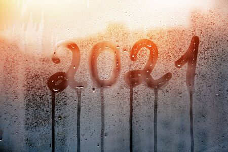 numbers 2021 of new year paint with finger with streaks of water on splashed by rain foggy glass on blue window and sunset Foto de archivo