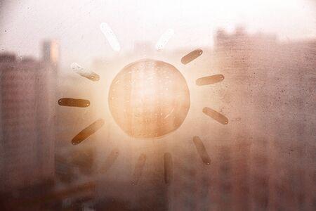 Hand drawn orange shape sun for text on muddy blue glass wet window in city on sunset 版權商用圖片