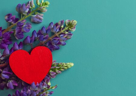 red wooden heart shape lies on fresh lupine flowers on a green textured surface, copy space