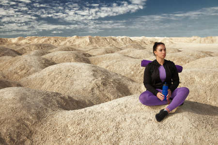 woman with backpack sitting on yellow dunes looks into distance on sunny day, copy space
