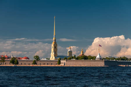 Peter and Paul Cathedral in Saint Petersburg beach and Neva river against backdrop of giant clouds and blue sky on sunny day, Russia