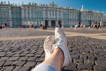 female legs in worn white macasinas on Palace Square in St. Petersburg, first-person view
