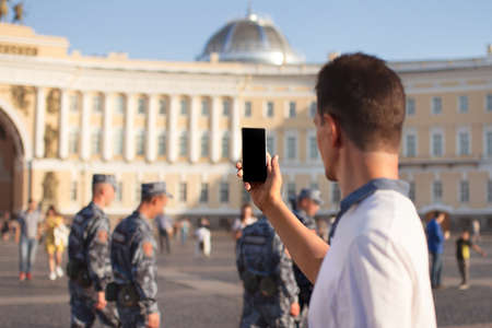 smartphone with black screen in hand of man in center of saint petersburg in front of military headquarters and marching military men, selective focus on phone