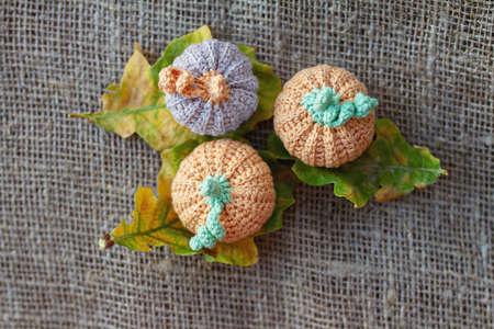 rural three crocheted handmade pumpkins on autumn oak leaves and bagging, selective focus