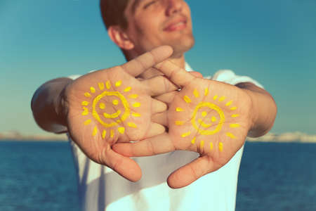 mens hand with paint yellow sun face and smile against blue sky, copy space, close up