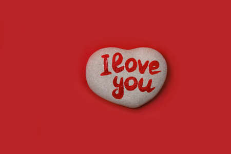 stone in shape of heart with inscription written by hand I love you on red background