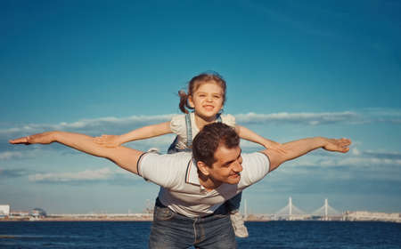 happy dad and daughter on beach: child 3 years old sitting on man s back with arms outstretched playing happy on plane on summer sunny day, copy space, concept, selective focus, film noise Stock fotó