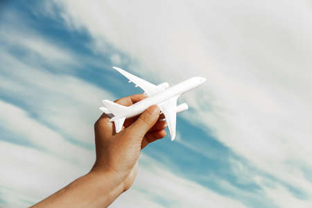 left male hand with white airplane up to left on blue sky cloudy background Foto de archivo