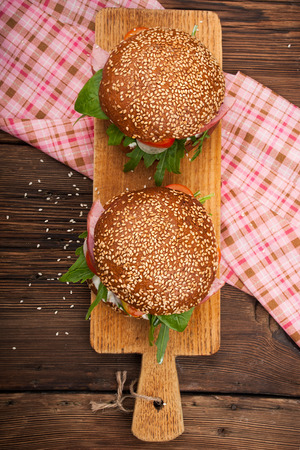 Burger with bacon, arugula and tomato on a wooden rustic background