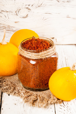Homemade sugar scrub with a pumpkin on a wooden background