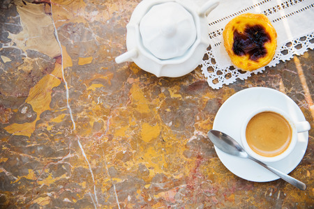 conceived: Conceived with the morning coffee and cakes (Pasteis de nata, typical pastry from Portugal) on natural marble surface.